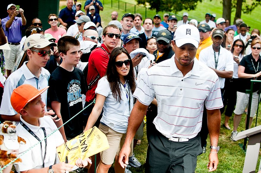 Tiger Woods walks past fans prior to his signing of the We Salute Our Troops wall at Congressional Country Club before the AT&T National golf tournament, Bethesda, Md., Tuesday, June 26, 2012.  The walls will be available to pros and fans to sign all week and will then be distributed for service members to view in a variety of military locations. (Ryan M.L. Young/The Washington Times)