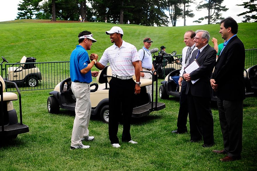 Charlie Wi, left, greets Tiger Woods at the 18th hole prior to Woods' signing of the We Salute Our Heroes wall at Congressional Country Club before the AT&T National golf tournament, Bethesda, Md., Tuesday, June 26, 2012.  The walls will be available to pros and fans to sign all week and will then be distributed for service members to view in a variety of military locations.  (Ryan M.L. Young/The Washington Times)