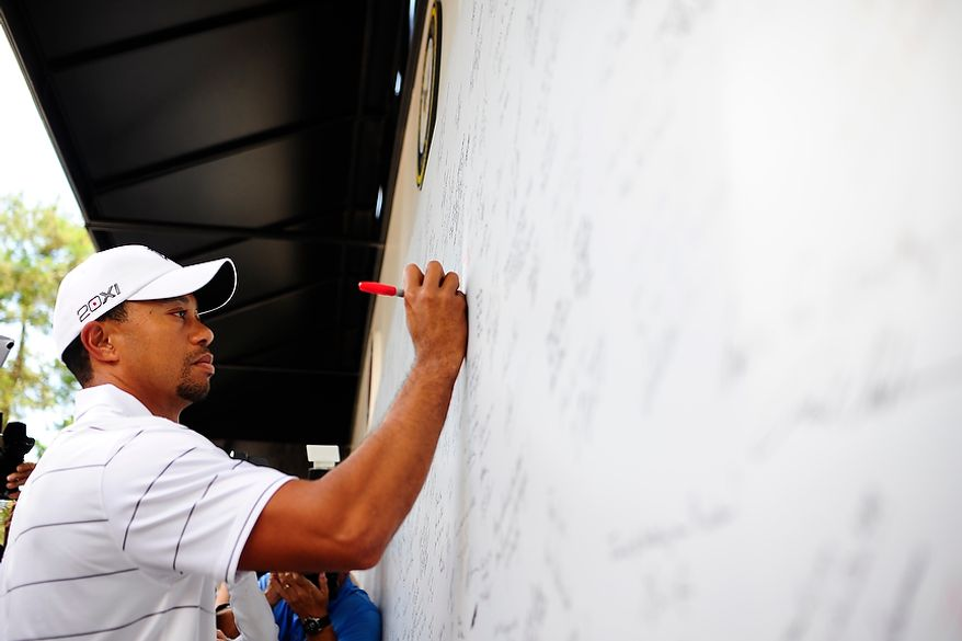Tiger Woods signs the We Salute Our Troops wall at Congressional Country Club before the AT&T National golf tournament, Bethesda, Md., Tuesday, June 26, 2012.  The walls will be available to pros and fans to sign all week and will then be distributed for service members to view in a variety of military locations.  (Ryan M.L. Young/The Washington Times)
