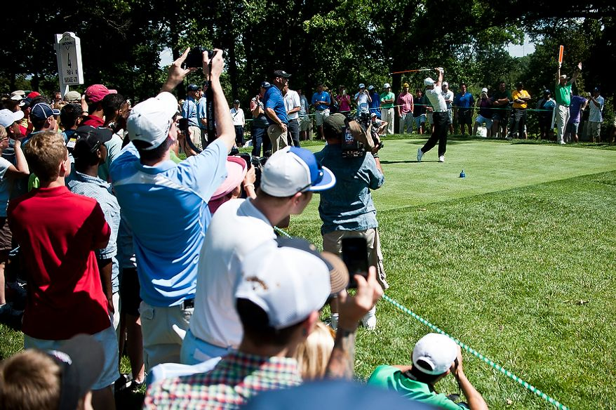 Tiger Woods tees off on the fourth hole as a gallery watches at Congressional Country Club before the AT&T National golf tournament, Bethesda, Md., Tuesday, June 26, 2012.  The tournament will begin on Thursday and runs until Sunday.  (Ryan M.L. Young/The Washington Times)