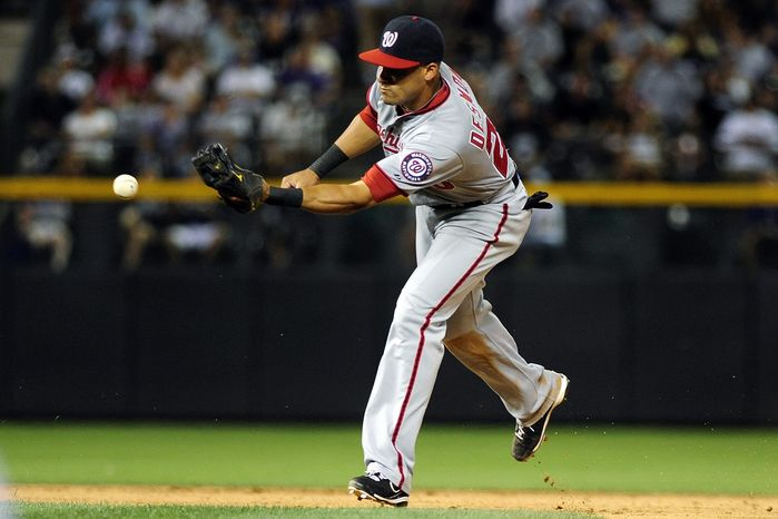 Washington Nationals shortstop Ian Desmond bobbles the catch allowing Colorado Rockies' Eric Young Jr. to steal second during the seventh inning of a baseball game, Monday, June 25, 2012, in Denver. (AP Photo/Jack Dempsey)
