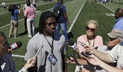 Washington Redskins quarterback Robert Griffin III talks to reporters on Tuesday, June 26, 2012, during a youth clinic as part of the NFL football rookie symposium at the Cleveland Browns training facility in Berea, Ohio. (Associated Press)