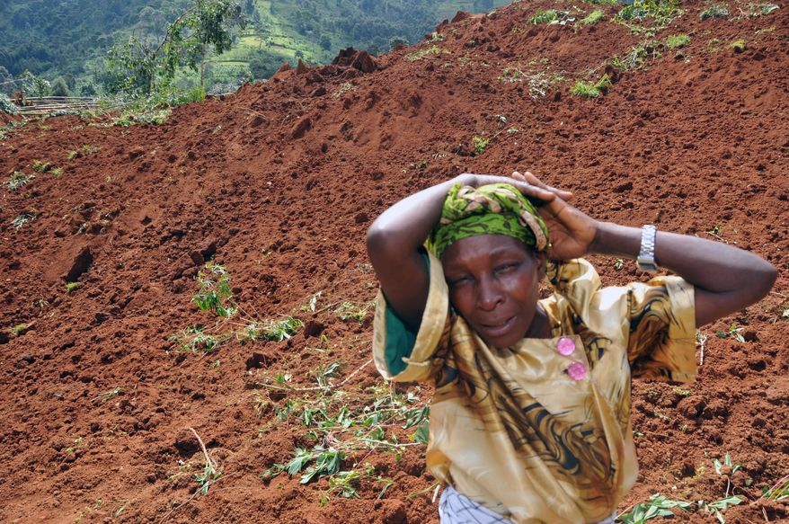 A woman cries for her four children, whom she lost in a landslide in Bududa, Uganda, on Tuesday, June 27, 2012. Massive mudslides induced by torrential rains destroyed three villages in the mountainous district of the country's east, killing scores of people, officials said. (AP Photo/Stephen Wandera)