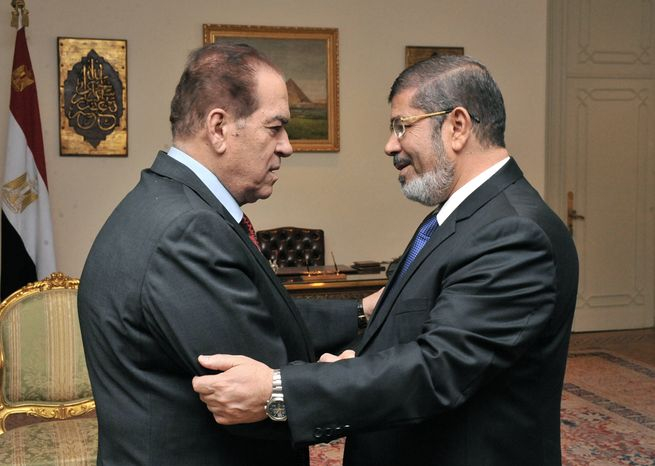 Kamal el-Ganzouri (left), Egypt's caretaker prime minister, shakes hands with Egyptian President-elect Mohammed Morsi in Cairo on Monday, June 25, 2012. (AP Photo/Middle East News Agency)