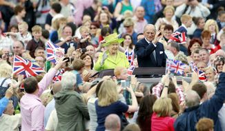 Queen Elizabeth II and Prince Philip wave to thousands of people at Stormont estate in Belfast on Wednesday. The queen and the Duke of Edinburgh continued their Northern Ireland visit to mark the queen's Diamond Jubilee. (Associated Press)