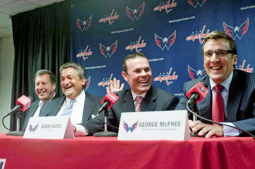 Capitals president Dick Patrick (left) , owner Ted Leonsis (second from left) , and general manager George McPhee (right) enjoy a light moment as Adam Oates is introduced as the team's coach at Verizon Center. Oates played parts of six seasons with Washington from 1997-2002. (Raymond Thompson/The Washington TImes)