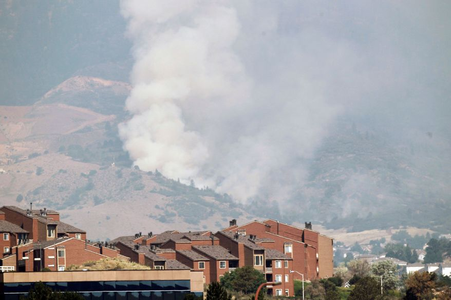 "A plume of smoke rises behind homes from the Waldo Canyon Fire west of Colorado Springs on Wednesday. ""It was like looking at the worst movie set you could imagine,"" Gov. John Hickenlooper said after flying over the 9-square-mile fire late Tuesday. (Associated Press)"