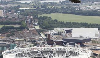 ** FILE ** An Aug. 18, 2011, photo released by Britain's Defense Ministry shows a Royal Air Force Puma helicopter flying over the 2012 Olympic Stadium during a training flight in London. (Associated Press/SAC Phil Major, Royal Air Force, Ministry of Defense)