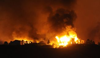Homes in the Mountain Shadows area of Colorado Springs, Colo., go up in flames from the Waldo Canyon fire on Tuesday, June 26, 2012. (AP Photo/The Gazette, Jerilee Bennett)