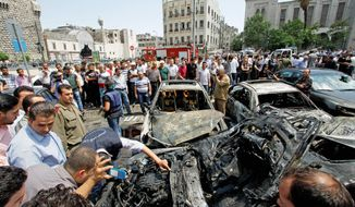 Syrians peer at cars damaged by an explosion Thursday afternoon in Damascus near the capital's famous Hamidiyeh Market and the Palace of Justice. State TV reported at least three people were wounded and about 20 cars damaged. (Associated Press)