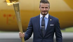 **FILE** Britain's David Beckham holds the Olympic torch during the May 18, 2012, ceremony at RNAS Culdrose, in Cornwall, England, to mark the arrival of the Olympic flame to Britain from Greece. (Associated Press)