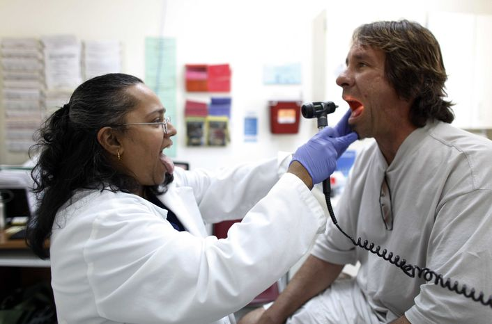 Dr. Hamsakumari Ramasubramaniam, left, examines patient Fabian Vasquez at Camillus Health Concern, Wednesday, June 27, 2012, in Miami. Camillus is a private, nonprofit organization that provides health care to the homeless and poor in Miami-Dade County. (AP Photo/Lynne Sladky)