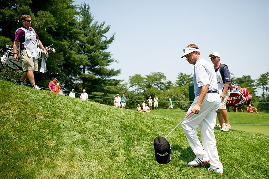 "Davis Love III, second from right, uses his club to pick up his caddy's hat after he gave him a ""hats off"" congratulations for his putt on the seventh hole on the first day of the AT&T National golf tournament held at Congressional Country Club, Bethesda, Md., Thursday, June 28, 2012. (Andrew Harnik/The Washington Times)"
