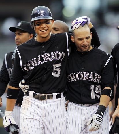 Colorado Rockies' Carlos Gonzalez, left, congratulates Marco Scutaro, right, after Scutaro's game-winning hit in the 11th inning of a baseball game against the Washington Nationals, Thursday, June 28, 2012, in Denver. The Rockies won 11-10 in 11 innings. (AP Photo/Chris Schneider)