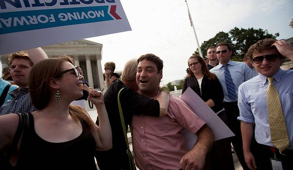 Donny Kirsch of Washington gets a hug as he celebrates the Supreme Court decision on health care, Thursday, June 28, 2012, in Washington.  (AP Photo/Evan Vucci)