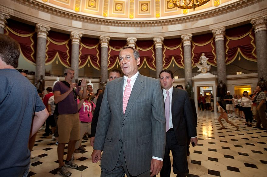 House Speaker John A. Boehner (center), Ohio Republican, walks toward the House chamber on Capitol Hill in Washington on Thursday, June 28, 2012, after the Supreme Court's ruling on President Obama's health care law. (AP Photo/Jacquelyn Martin)
