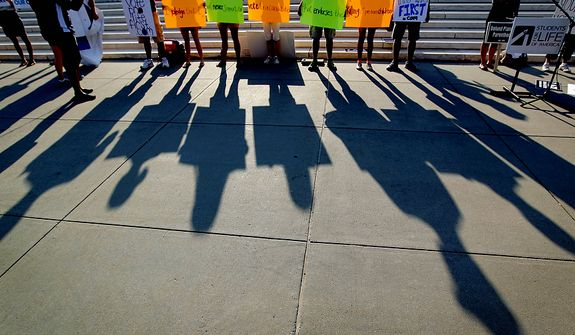 Protestors shadows are cast outside the Supreme Court in Washington, Thursday, June 28, 2012, in Washington, as the Supreme Court is expected to announce its verdict on President Barack Obama's health care law. (AP Photo/David Goldman)