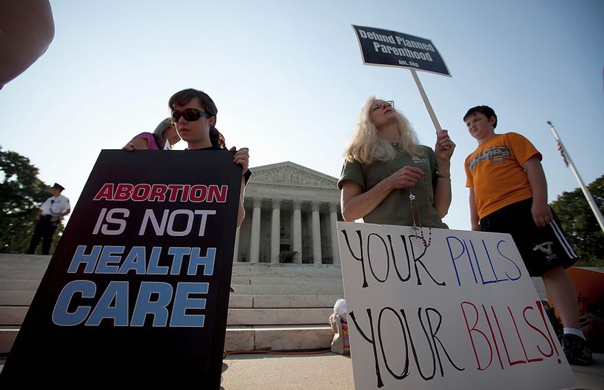 Demonstrators pray outside the Supreme Court in Washington, Thursday, June 28, 2012, before a landmark decision on health care.  (AP Photo/Evan Vucci)
