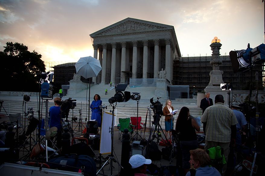 Journalists wait outside the Supreme Court for a landmark decision on health care on Thursday, June 28, 2012 in Washington.  (AP Photo/Evan Vucci)
