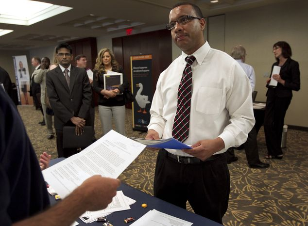 Trey Fortes (right) speaks with Jason Monteiro (left) of Hudson, Mass., during a job fair in Boston on Monday, June 18, 2012. (AP Photo/Steven Senne)