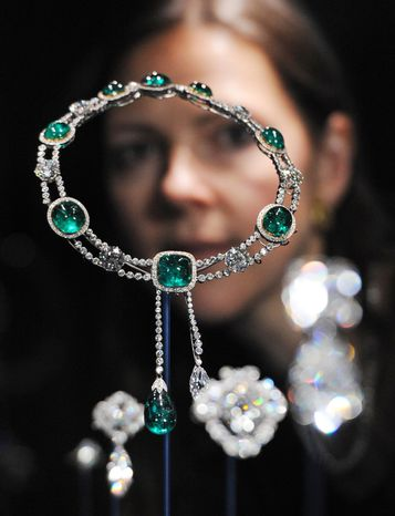 Curator Caroline de Guitaut stands behind the Delhi Durbar necklace and Cullinan pendant made up of diamonds and emeralds, created for the Delhi Durbar of 1911 and owned by Queen Mary, at a new exhibition at Buckingham Palace in London on June 28, 2012. The exhibition shows jewels collected by six monarchs over three centuries to mark the Queen's Diamond jubilee this summer. (Associated Press/Stefan Rousseau/PA Wire)
