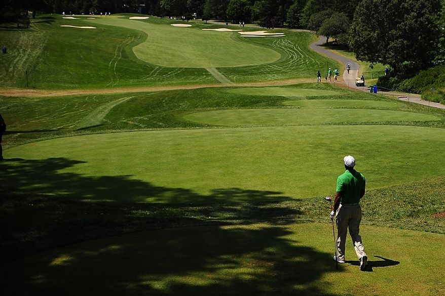 Tiger Woods walks down the first fairway at Congressional Country Club during third round play of the AT&T National golf tournament, Bethesda, Md., Saturday, June 30, 2012.  (Ryan M.L. Young/The Washington Times)