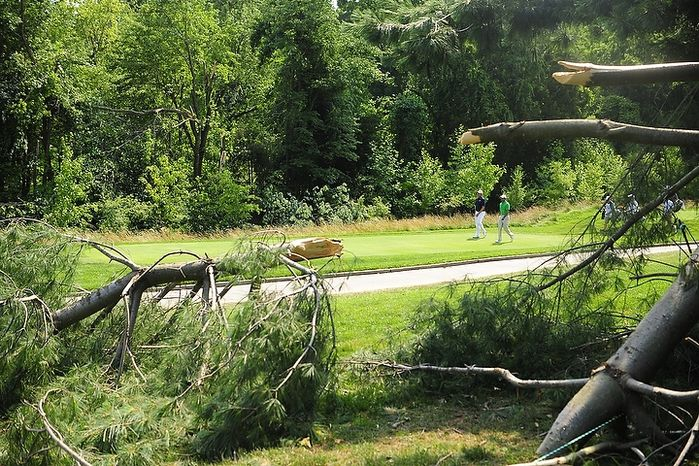 Tiger Woods and Bo Van Pelt walk past downed tree limbs on the sixth hole at Congressional Country Club during third round play of the AT&T National golf tournament, Bethesda, Md., Saturday, June 30, 2012.  The tournament was closed to the public on S