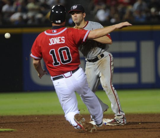 Washington Nationals second baseman Danny Espinosa sends the ball past Atlanta Braves' Chipper Jones on a double play hit into by Matt Diaz during the eighth inning of a baseball game, Friday, June
