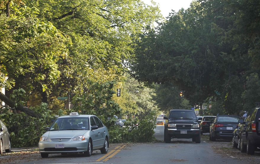 A fallen tree blocks one lane of traffic on 13th Street NW in the Logan Circle neighborhood of Washington, Saturday, June 30, 2012. Violent evening storms following a day of triple-digit temperatures wiped out power to more than 2 million people across the eastern United States. (AP Photo/Pablo Martinez Monsivais)