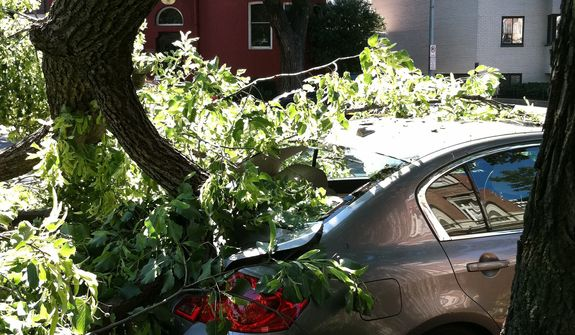 A tree toppled by severe storms sits atop a car in Washington's Dupont Circle neighborhood on Saturday, June 30, 2012, in Washington. More than two million people across the eastern U.S. lost power after violent storms and two people died, including a 90-year-old woman asleep in bed when a tree slammed into her home, a police spokeswoman said Saturday. (AP Photo/Jessica Gresko)