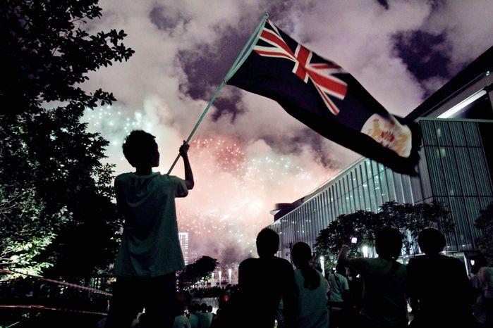 A protester waves a Hong Kong colonial flag Sunday during the annual demonstration for democracy there. A pro-democracy heckler interrupted a speech by Chinese President Hu Jintao at the swearing-in of Hong Kong's new leader, and tens of thousands of residents marched