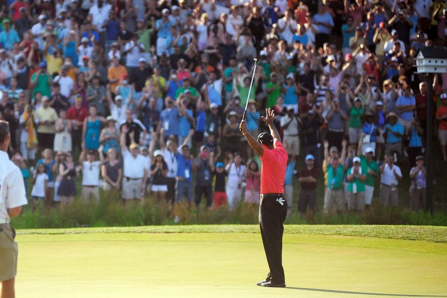 Tiger Woods raises his hands in victory on the 18th green Sunday at the AT&T National at Congressional Country Club. Woods shot a final-round 69 to beat Bo Van Pelt by two strokes. (Ryan M.L. Young/The Washington Times)