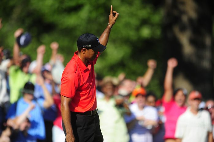 Tiger Woods raises his hand as he sinks a birdie putt on the fifteenth hole at Congressional Country Club during final round play of the AT&T National golf tournament, Bethesda, Md., Sunday, July 1, 2012.  (Ryan M.L. Young/The Washington Times)