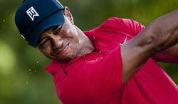 Beads of sweat fly off of Tiger Woods' face as he hits his tee shot on the seventeenth hole at Congressional Country Club during final round play of the AT&T National golf tournament, Bethesda, Md., Sunday, July 1, 2012.  (Ryan M.L. Young/The Washington Times)