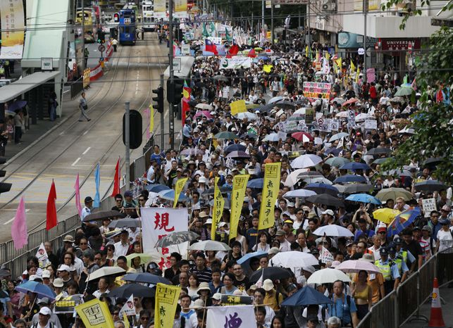 Tens of thousands of Hong Kong residents take part in an annual pro-democracy march in Hong Kong on Sunday, July 1, 2012. (AP Photo/Kin Cheung)