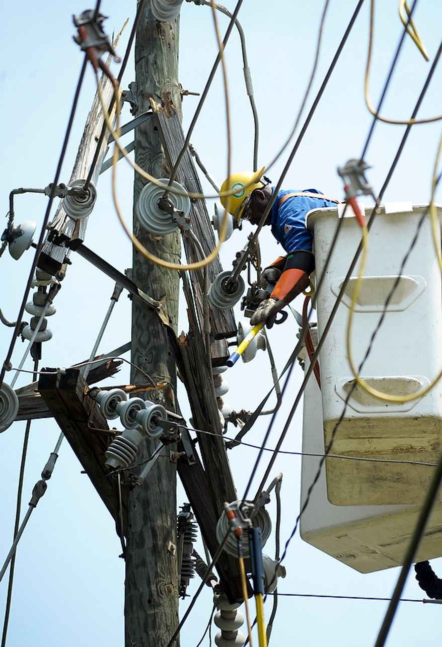 A utility worker secures a power line on a pole as his team repairs lines downed by fallen trees in Springfield, Va., Sunday, July 1, 2012. A severe storm late Friday, June 29th knocked out power to approximately one million residents, traffic signals and businesses in the region. (AP Photo/Cliff Owen)