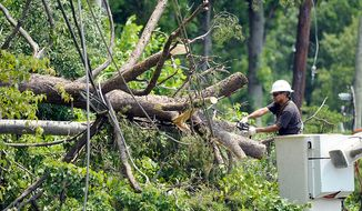 A utility worker clears a downed tree in Springfield, Va., Sunday, July 1, 2012. A severe storm late Friday knocked out power to approximately one million residents, traffic signals and businesses in the  region.  (AP Photo/Cliff Owen)