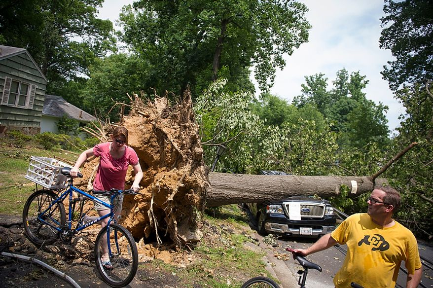 Erin Hodges (left) and her fiance John Hopewell, both of Falls Church, Va., tour the destruction from the front yard of home owner Mike Wolfe on N.Virginia Avenue in Falls Church, Va., Sunday, July 1, 2012, two days after a deadly, severe storm left hundreds of thousands of people without power. (Rod Lamkey Jr./The Washington Times)