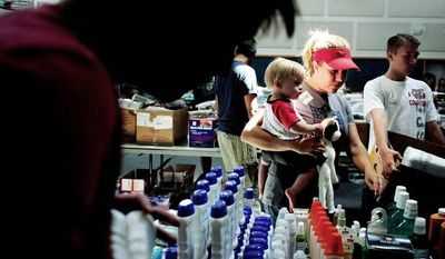 Volunteer Esther Fleece carries her friend's child, Nolan, through rows of relief supplies at the New Life Church on Saturday. Gleaning for the World, an organization based in Concord, Va., donated four semi-trailers worth of supplies toward the relief efforts. (Associated Press)