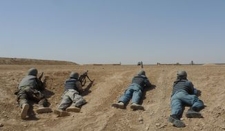 Afghan soldiers and policemen stage a mock ambush as part of a training exercise at the U.S. Marine-run Joint Sustainment Academy at Camp Leatherneck in Afghanistan's Helmand province on Tuesday, June 19, 2012. (AP Photo/Heidi Vogt)