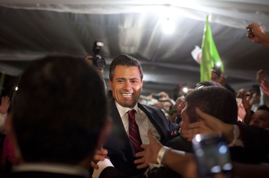 Enrique Pena Nieto, presidential candidate for the Revolutionary Institutional Party (PRI), greets supporters at his party's headquarters in Mexico City early on Monday, July 2, 2012. (AP Photo/Alexandre Meneghini)