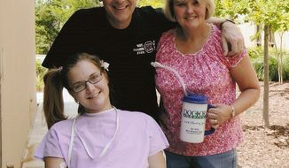 **FILE** Aimee Copeland (left) poses June 23, 2012, with her parents, Andy and Donna Copeland, outside Doctors Hospital in Augusta, Ga. Aimee Copeland had her left leg, right foot and both hands amputated after she was diagnosed with a rare, flesh-eating disease. (Associated Press/Copeland Family)