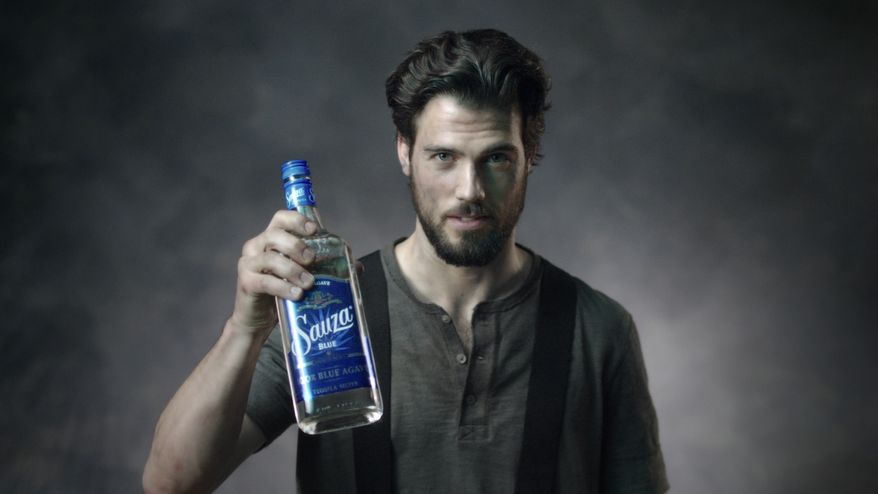 """This image from video released by Sauza shows a fireman holding a bottle of Sauza Tequila for a video directed by Matt Lenski for the """"Make it with a Fireman"""" campaign. The ad, launched in April, reflects a shift in spirits marketing as some producers look beyond traditional male-oriented campaigns. (AP Photo/Sauza)"""