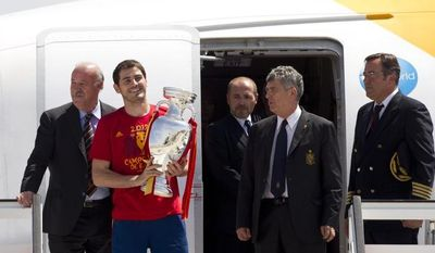 Iker Casillas (second from left), captain of the Spanish national soccer team, holds the Euro 2012 championship trophy alongside coach Vicente del Bosque (left) and Angel Villar (fourth from left), president of the Spanish football association, upon their arrival at Madrid's Barajas Airport on Monday, July 2, 2012. (AP Photo/Paul White)