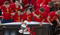 Spain's Pedro Rodriguez, center, holds the trophy as he celebrates with team mates on top of an open-deck bus in Madrid Monday July 2, 2012. Spain won the Euro 2012 soccer championship final against Italy in Kiev, Ukraine, Sunday. (AP Photo/Paul White)