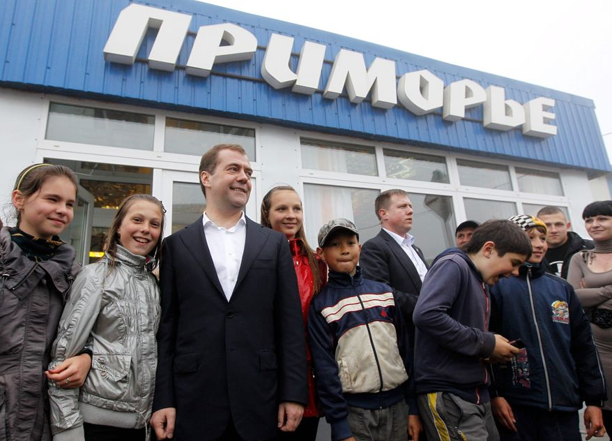 Russian Prime Minister Dmitry Medvedev poses Tuesday with children in front of a store he visited on one of the Kuril Islands. Mr. Medvedev pledged to boost aid for four impoverished islands, ownership of which has been disputed by Tokyo since World War II. (Associated Press)