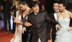 Hong Kong movie star Jackie Chan, center, escorts other actors on the red carpet prior to the opening ceremony of the Shanghai International Film Festival at Shanghai Grand Theater Saturday, June 16, 2012, in Shanghai, China. (AP Photo/Eugene Hoshiko)