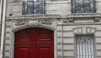 Members of the media are seen July 3, 2012, at the entrance of the building housing the offices of former French President Nicolas Sarkozy in Paris. French investigators searched Sarkozy's home and office earlier that day as part of a probe into suspected illegal financing of his 2007 presidential campaign by the L'Oreal cosmetics heiress, an official said. (Associated Press)