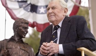 "Actor Andy Griffith sits in front of a bronze statue of Sheriff Andy Taylor and son Opie from ""The Andy Griffith Show"" after the unveiling ceremony in Raleigh, N.C., in October 2003. (AP Photo/Bob Jordan)"