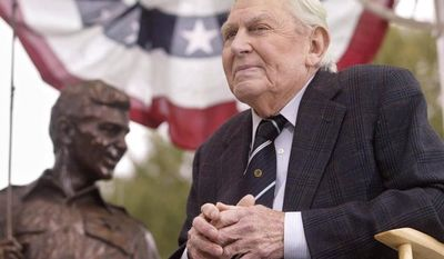 """Actor Andy Griffith sits in front of a bronze statue of Sheriff Andy Taylor and son Opie from """"The Andy Griffith Show"""" after the unveiling ceremony in Raleigh, N.C., in October 2003. (AP Photo/Bob Jordan)"""